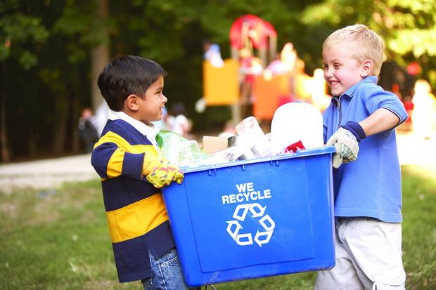 kids carrying recycling bin