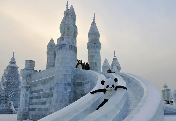An employee wearing a panda costume slides down from an ice sculpture during the Harbin International Ice and Snow World festival in Harbin