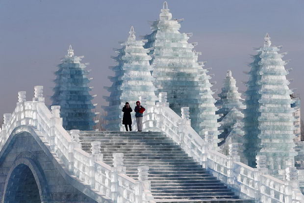 Visitors walk around ice sculptures during the annual ice festival in Harbin, Heilongjiang province