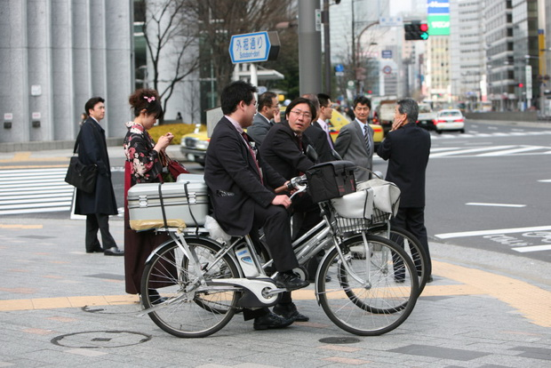 Japanese people stand at a crosswalk waiting for the green traffic light