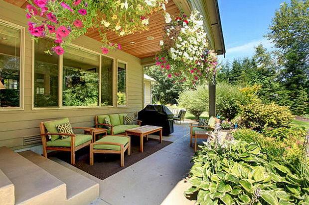 Cozy backyard concrete floor patio area with table set. Northwest, USA